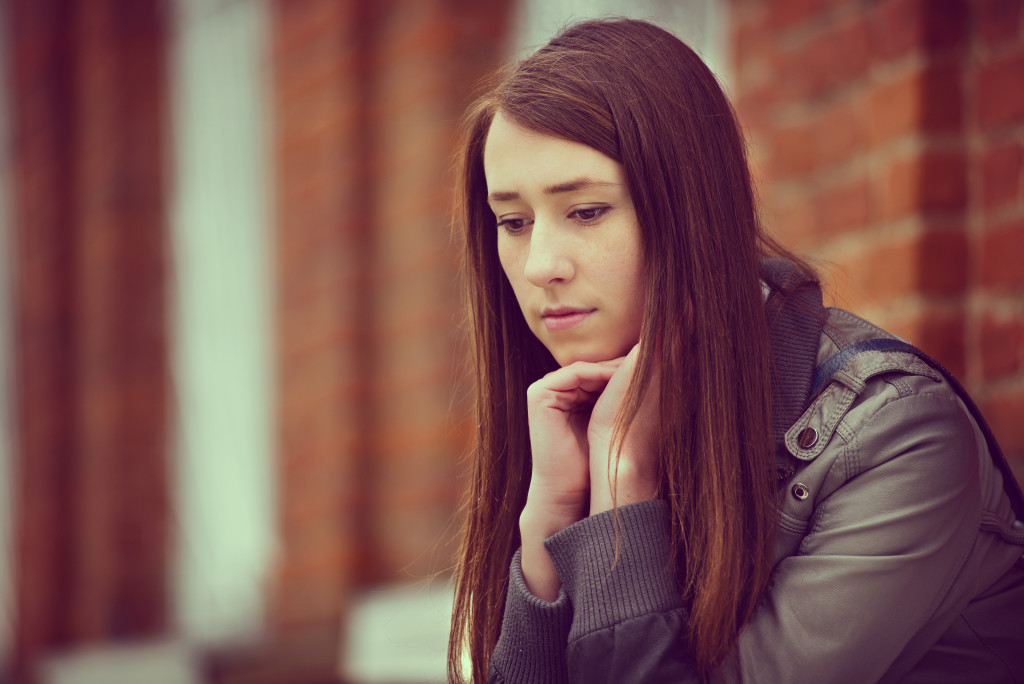 Thoughtful depressed young woman sitting with her chin on her hands outside a brick building staring down at the ground