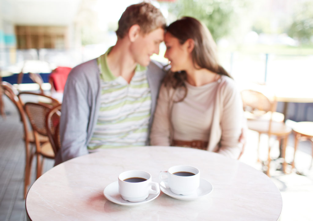 Image of two cups of coffee on table with romantic couple on background