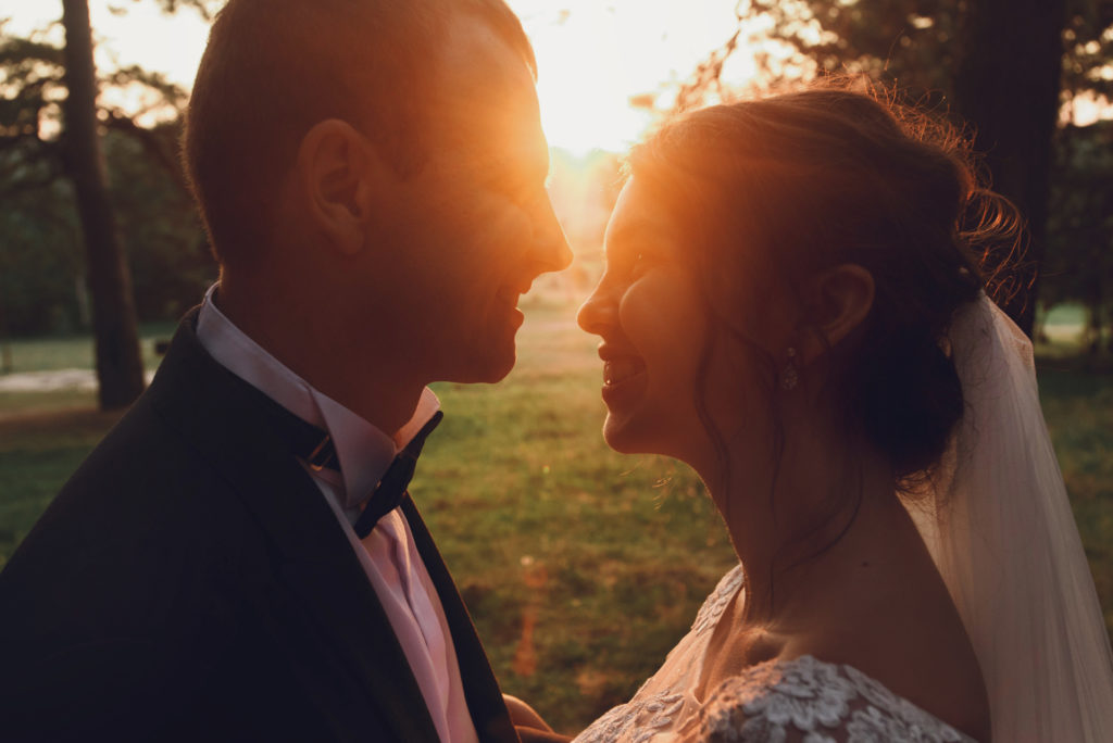 gorgeous elegant happy bride and stylish groom on the background of beautiful sunset in forest